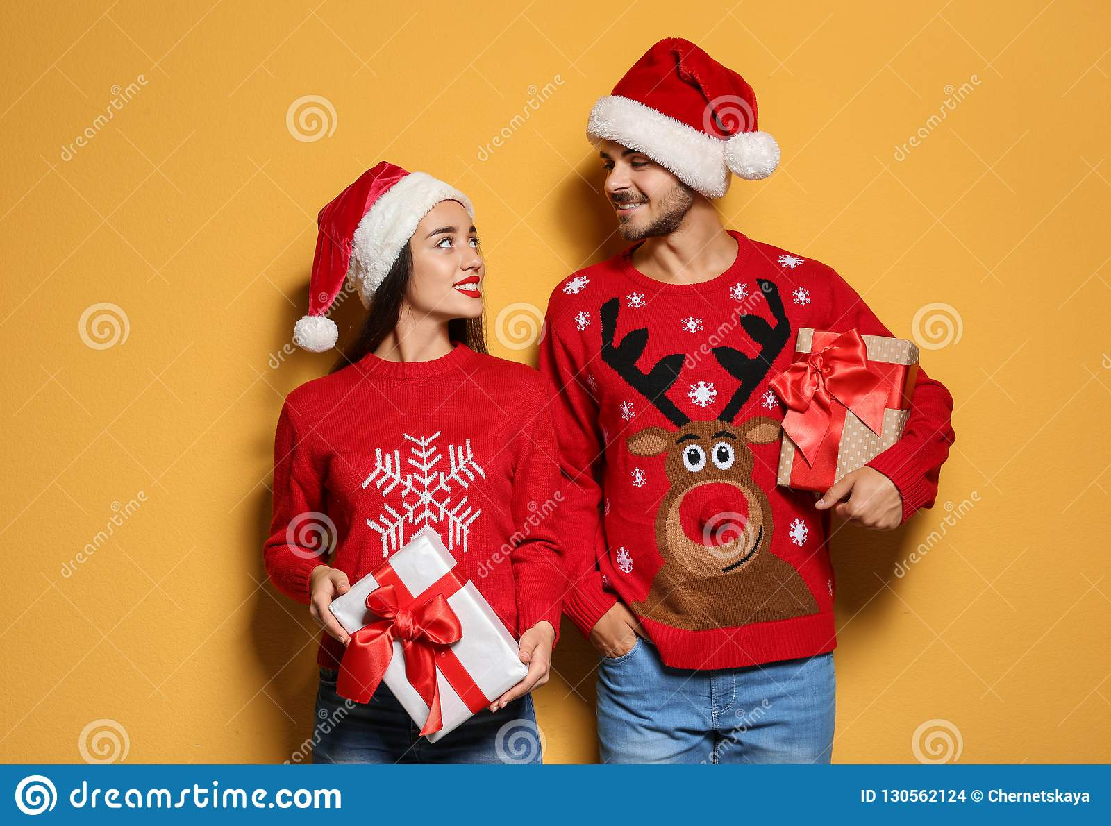 Young couple in Christmas sweaters and hats with gifts