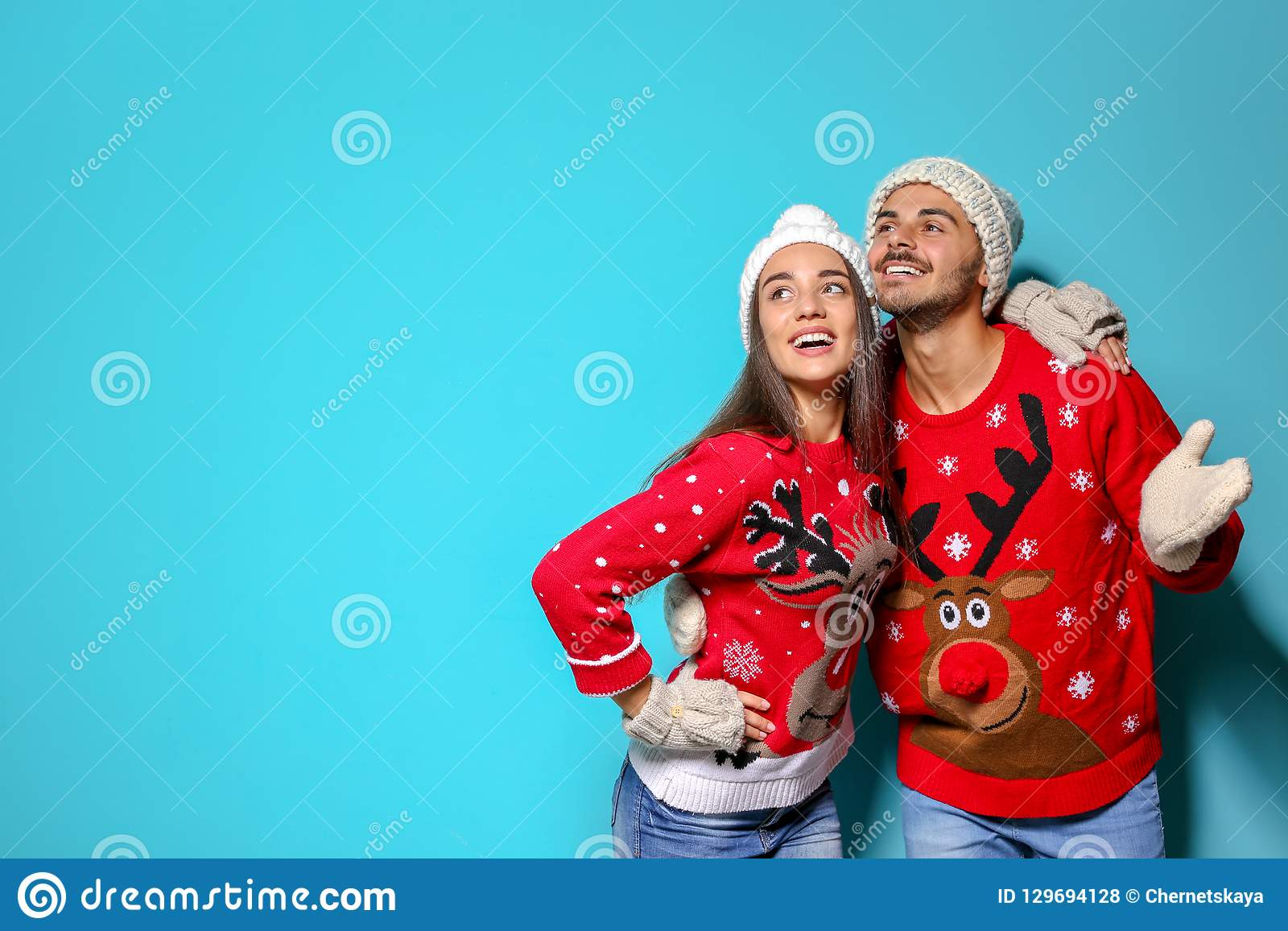 Young couple in Christmas sweaters and knitted hats on color background.
