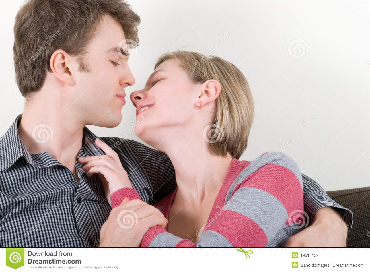 romantic teenage couple kissing on sofa at home stock photography 18031688. Black Bedroom Furniture Sets. Home Design Ideas