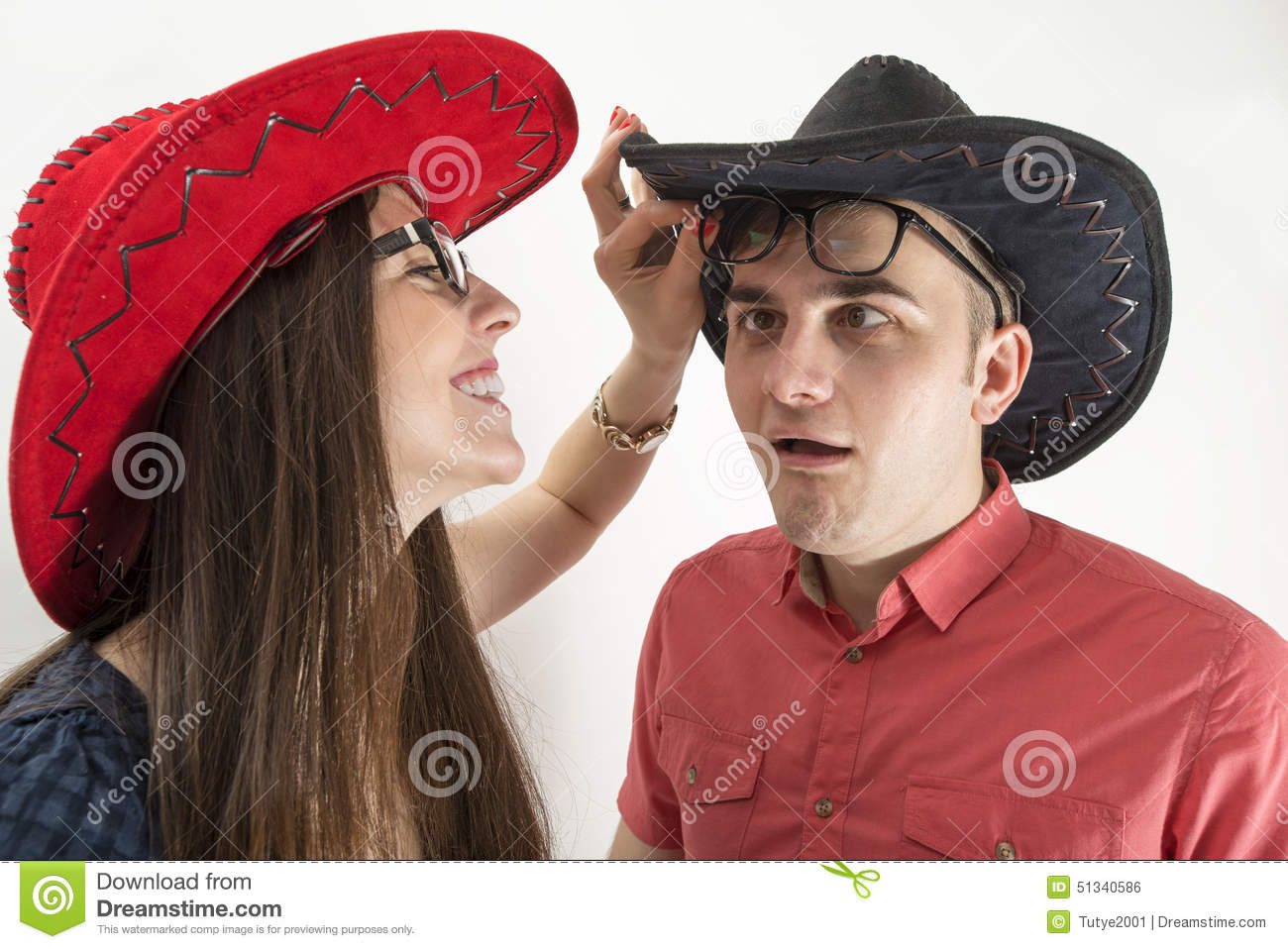 Young couple with cowboy hats and glasses making silly faces on white 863b9e7a9f5