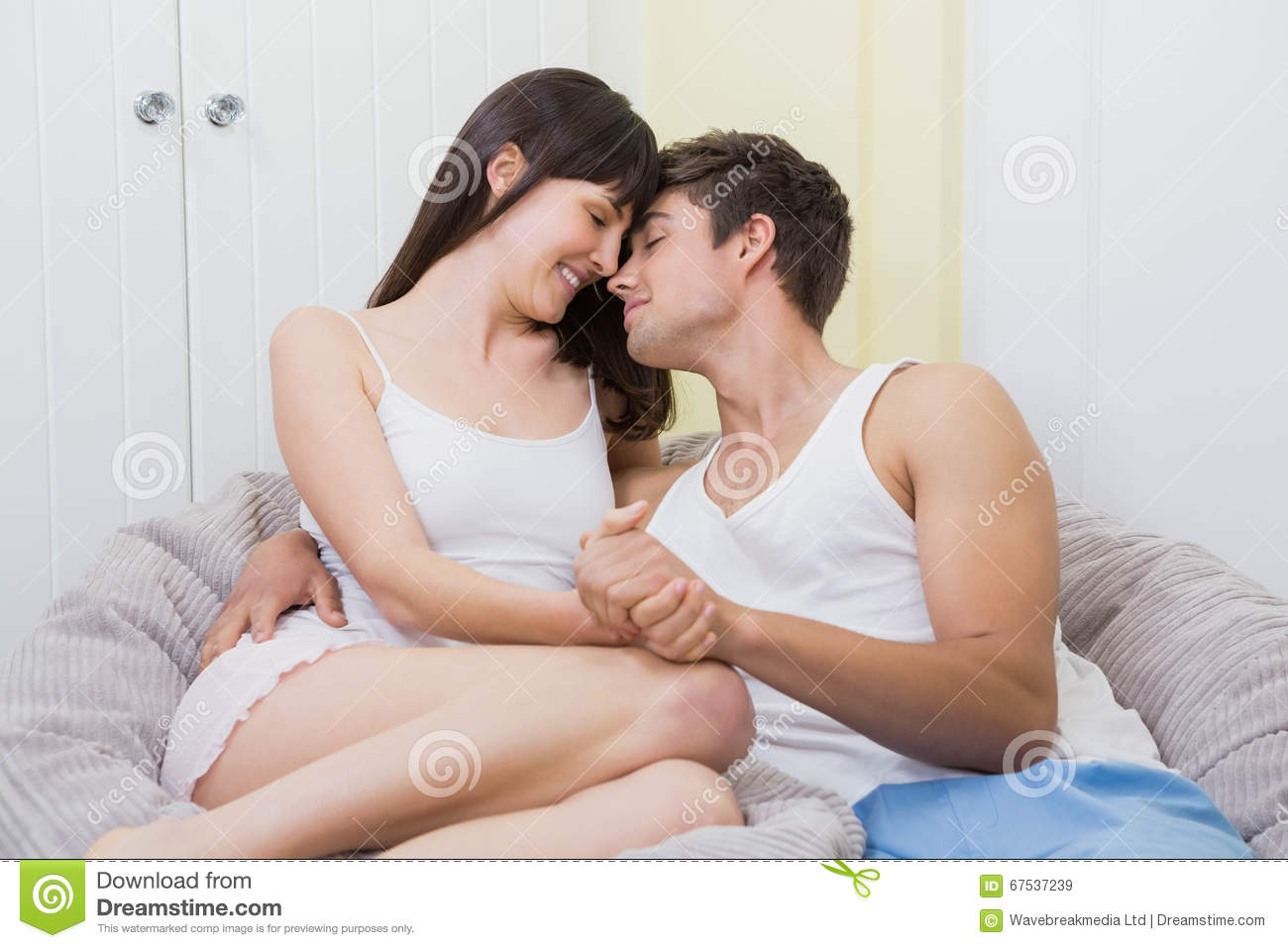 Download Young Couple Cuddling On Sofa Stock Image   Image Of Comfortable,  Brunette: 67537239