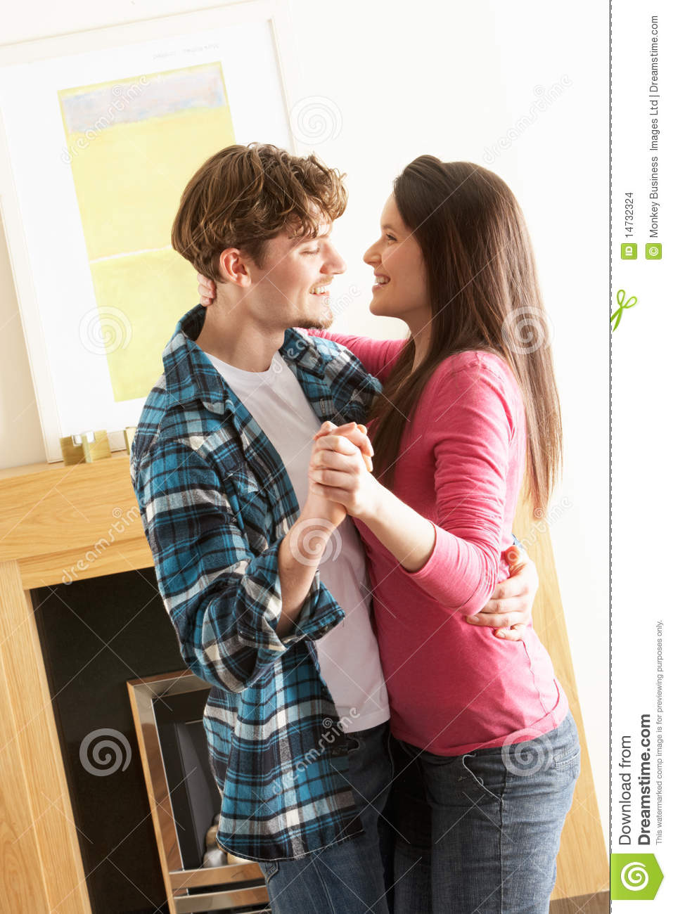 young couple dancing together in living room stock photo