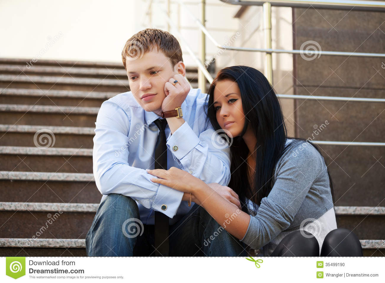 Sad young couple in depression sitting on the steps