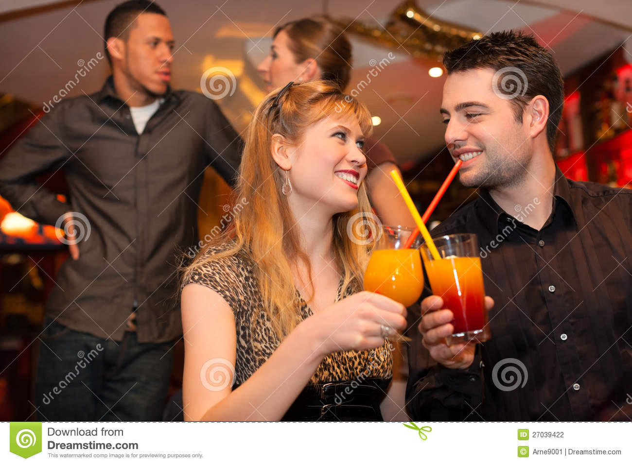 Young couple drinking cocktails in ba