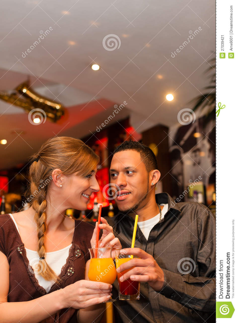 Young couple drinking cocktails in bar