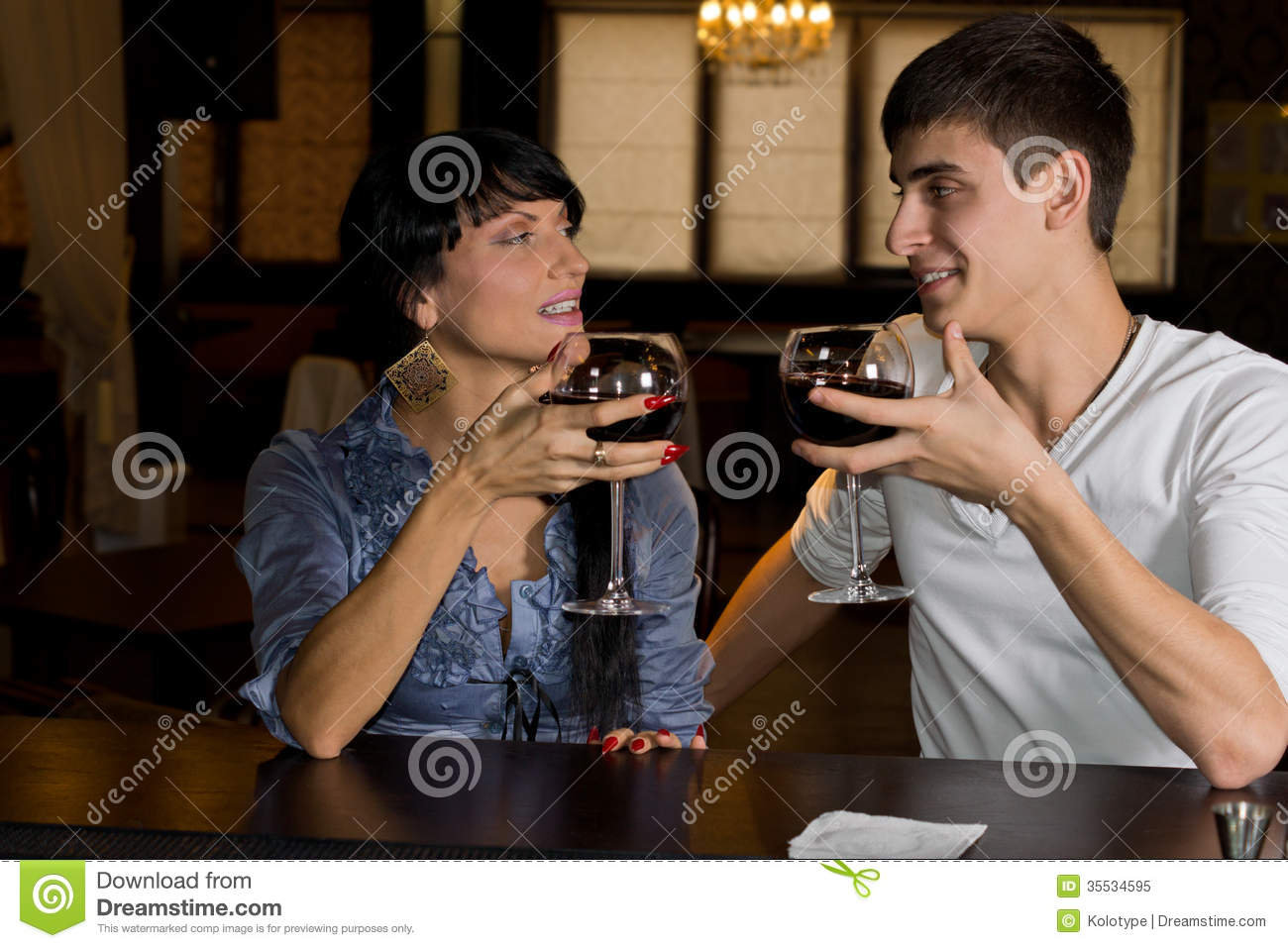 Young couple drinking red wine at a bar counter