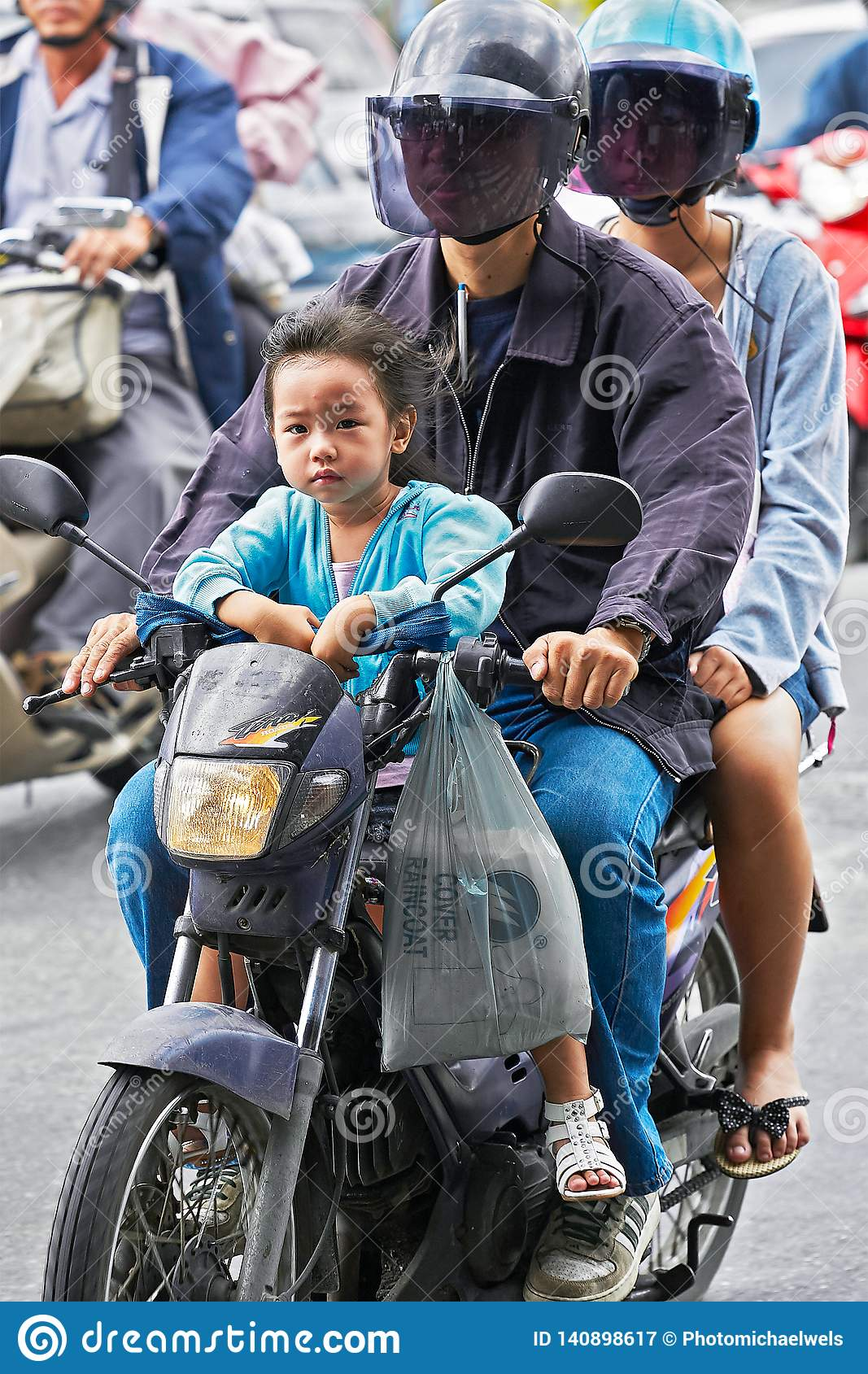 A young couple driving on a motorbike in Bangkok traffic