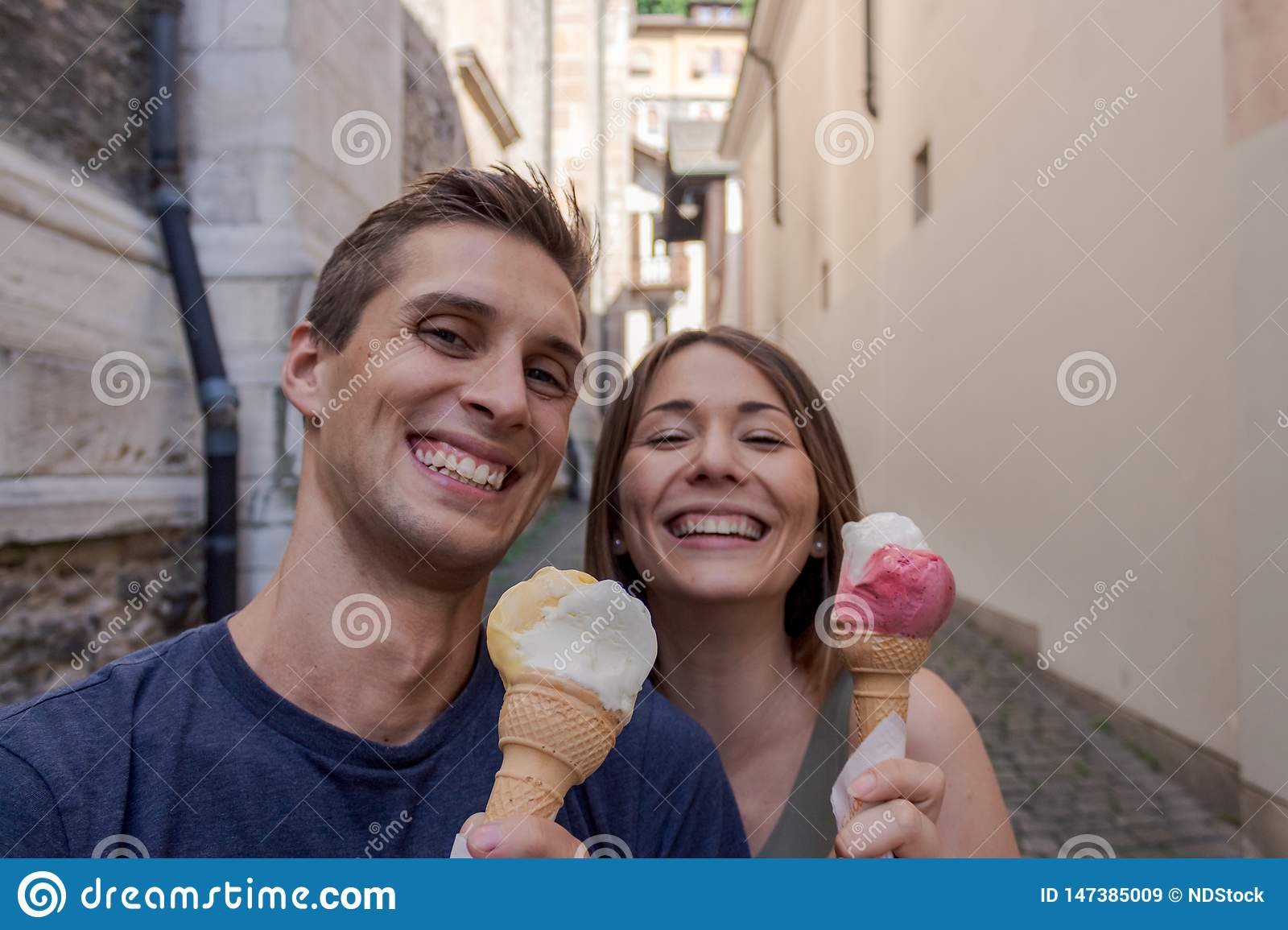 Young couple eating ice cream in an alley