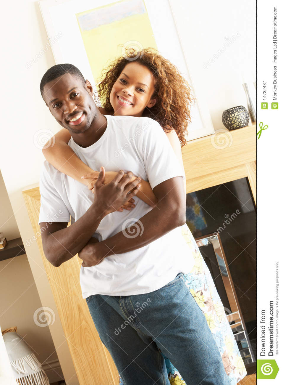 Young couple embracing in living room royalty free stock for Living room ideas young couples