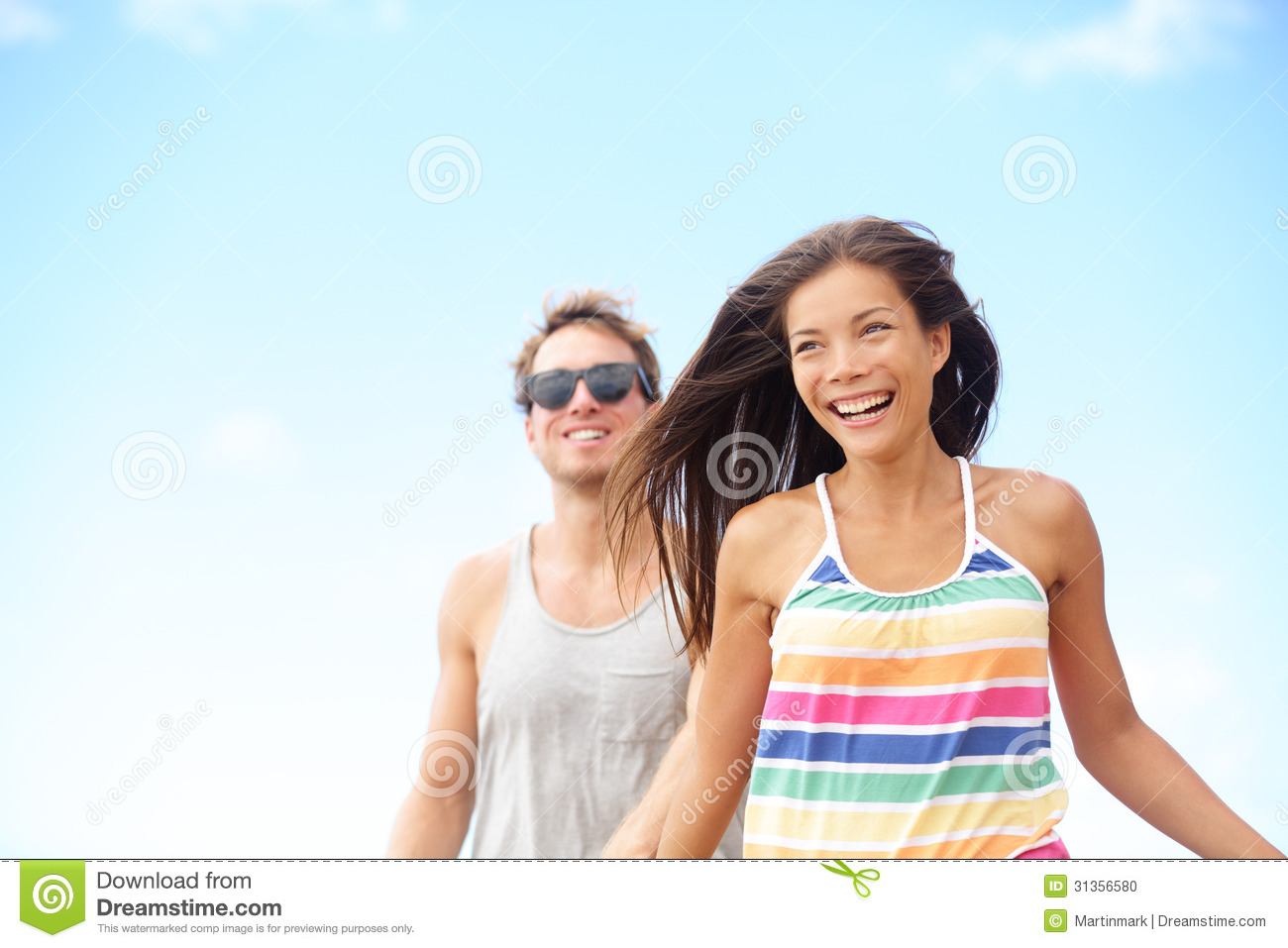 Young couple enjoying beach fun laughing running stock for Cool vacations for couples