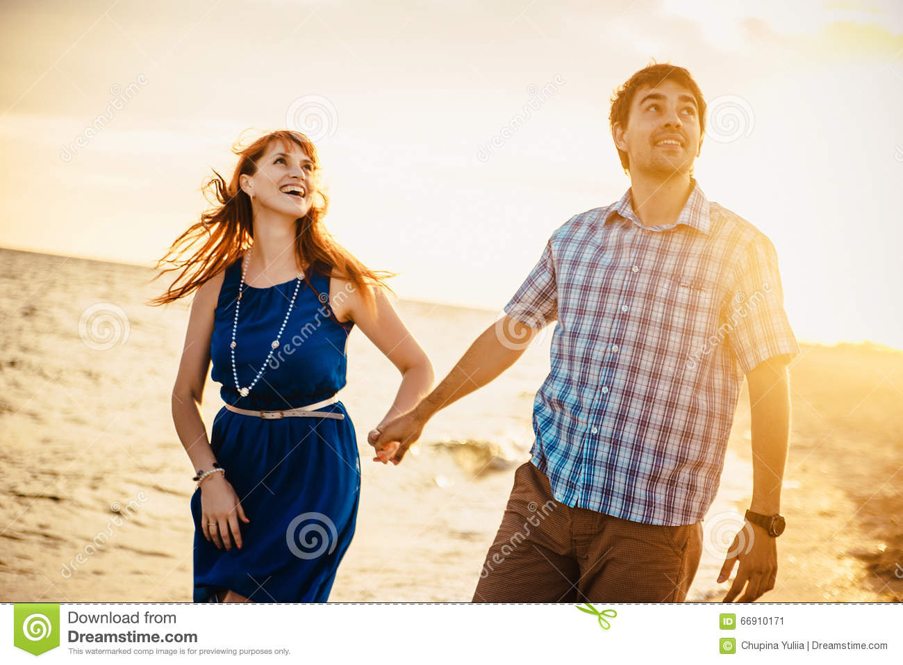 A young couple enjoys a mid summer late afternoon, on a wet san