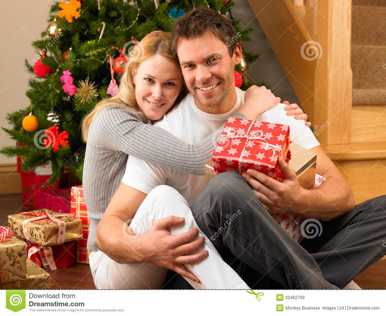 Young Couple With Gifts In Front Of Christmas Tree Stock Image ...