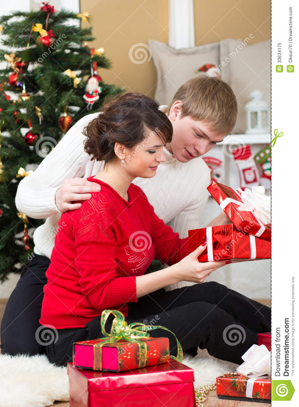 Young couple with gifts in front of christmas tree royalty Unique christmas gifts for couples who have everything