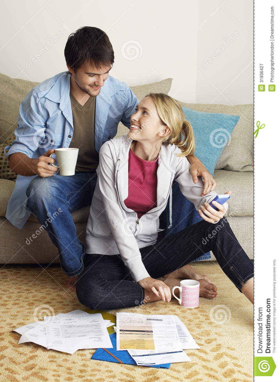 Young couple happily calculating expenses royalty free for Living room ideas young couples