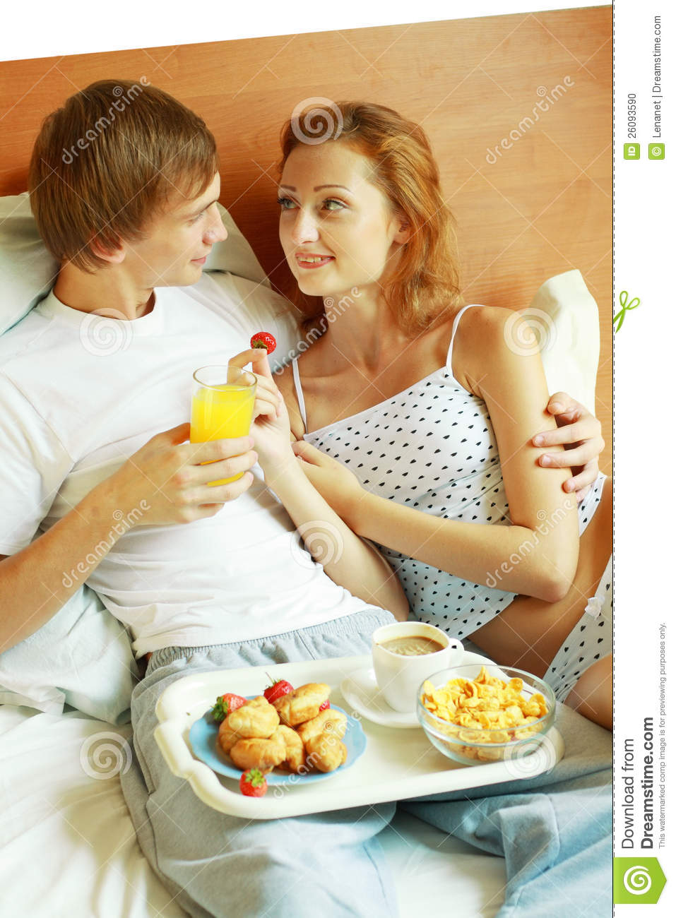 Relaxed young couple lying on bed comfortably with served breakfast in ...