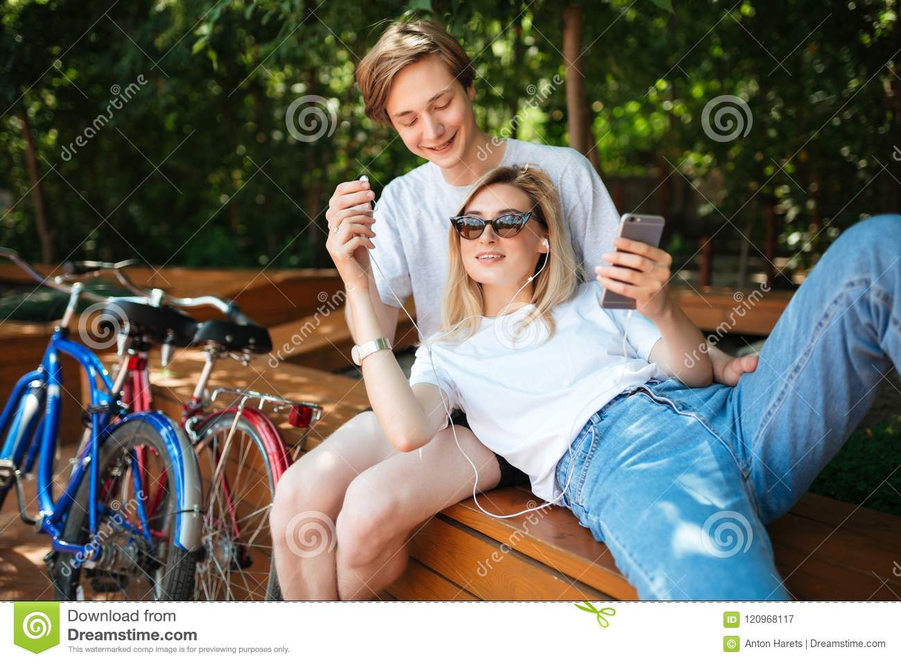 Young couple having fun while spending time in park with two bicycles nearby. Boy sitting on bench in park happily