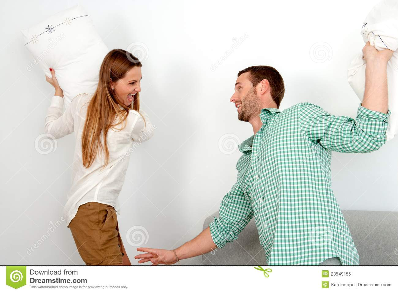nude couples pillow fighting