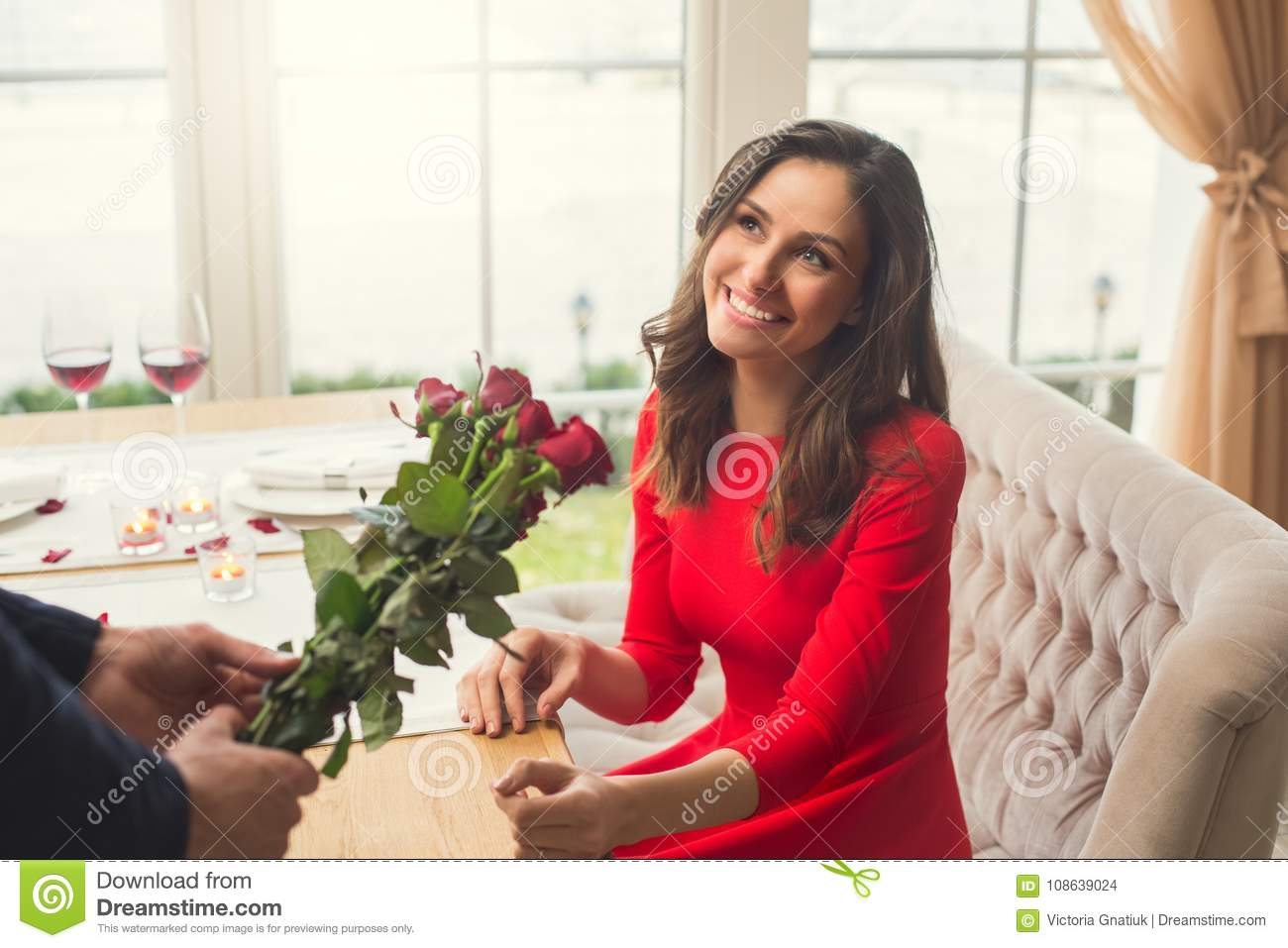 Young Men Giving Flowers To A Women Having Romantic Dinner In The Restaurant Smiling