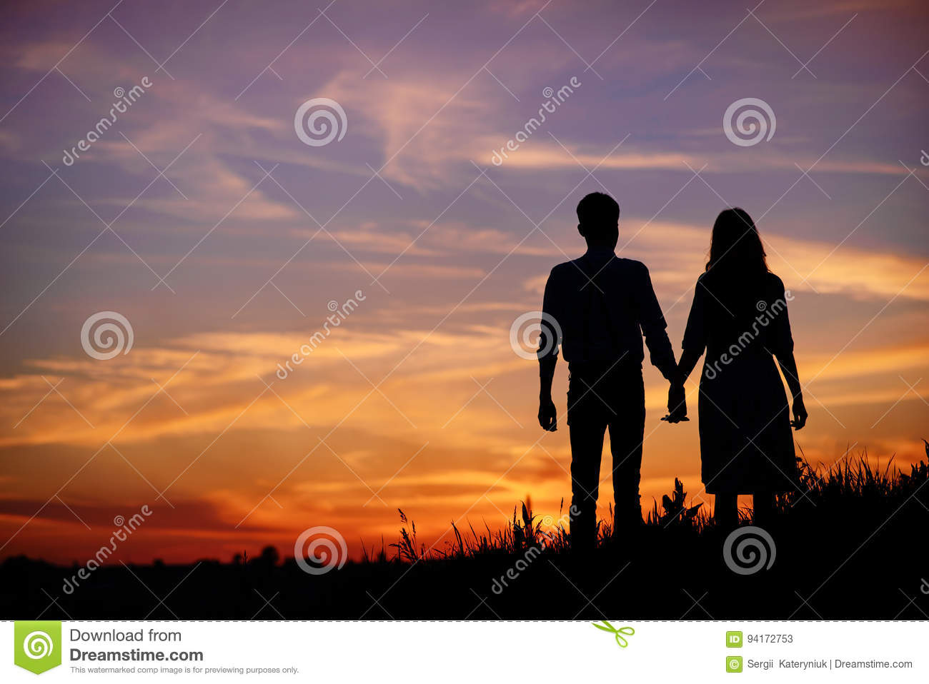 Young Couple Is Holding Hands On A Background Sunset Silhouette ... for Couple Holding Hands Silhouette Sunset  21ane