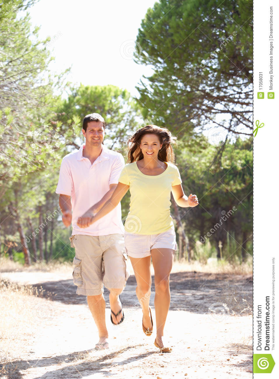 Young couple  holding hands  walking walk in park in the sun Young Couple Walking In The Park