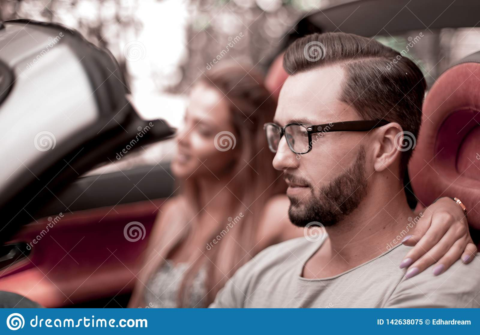Young couple inside a convertible car for a day trip.