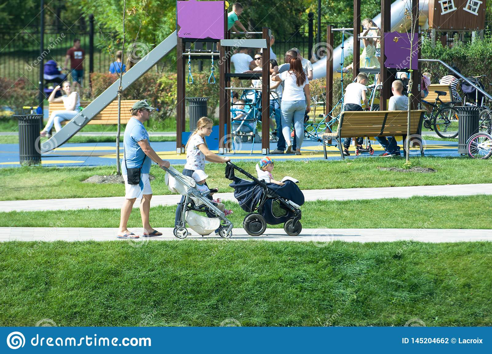 Young couple with kids stroller walking in Butovo park, Moscow, Russia