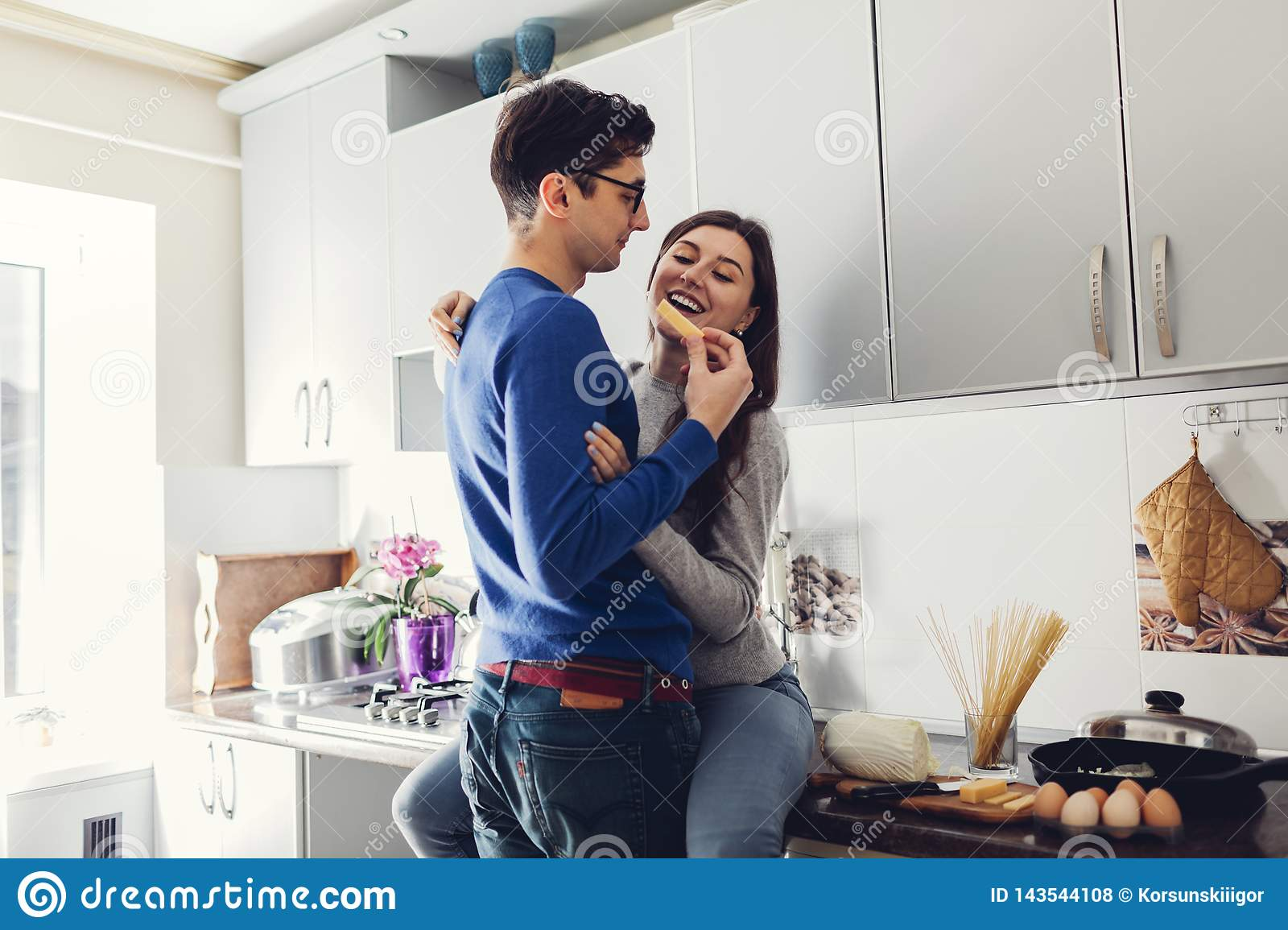 Young couple in the kitchen hugging and eating cheese.