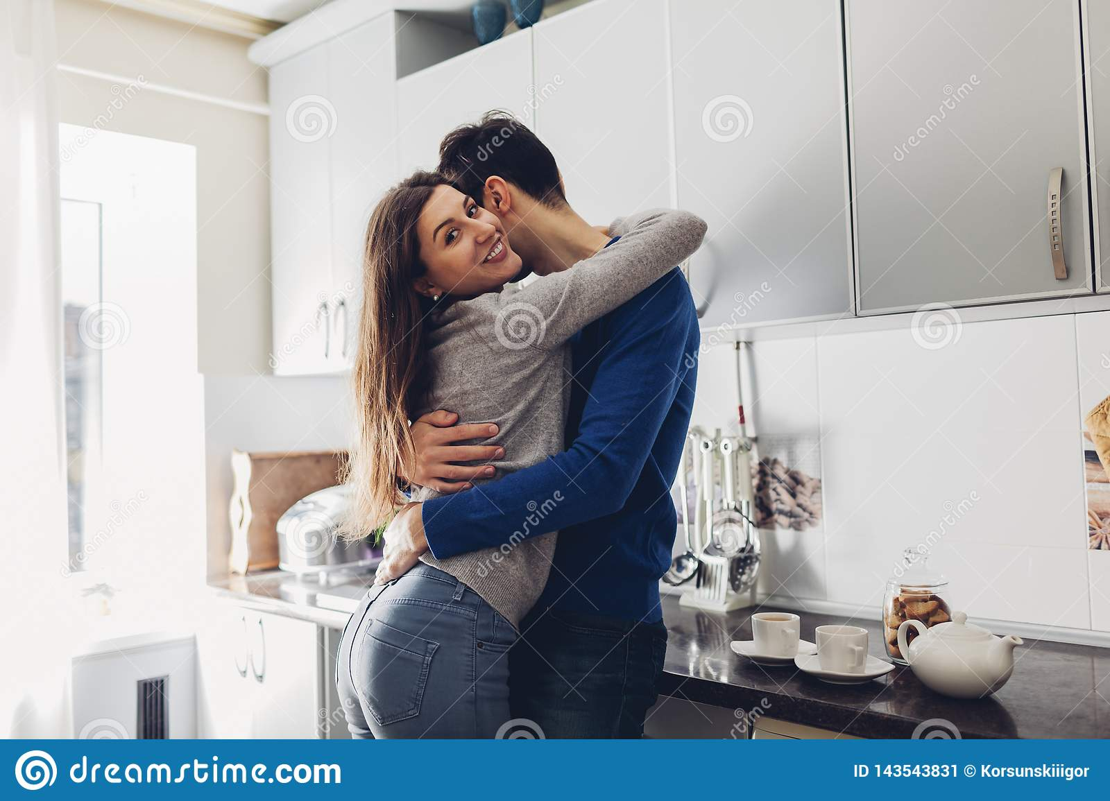 Young couple in the kitchen hugging and making tea
