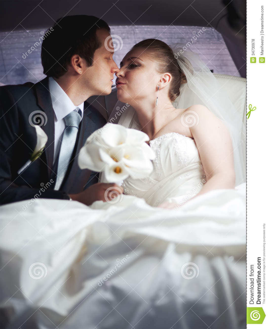 Newlywed young couple in limo kissing. wedding picture