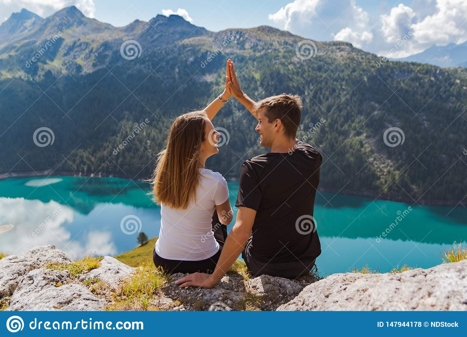 Young couple in love beating high five on a rock with a beautiful panorama as background. Swiss alps