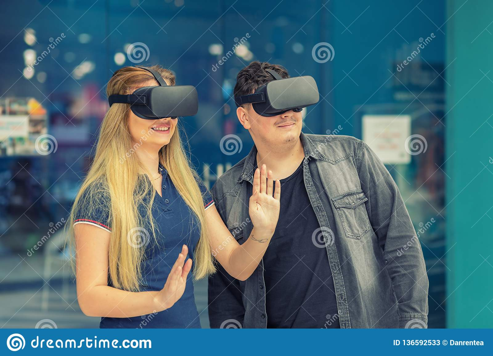 Young couple in love connecting through virtual reality glasses in playground center