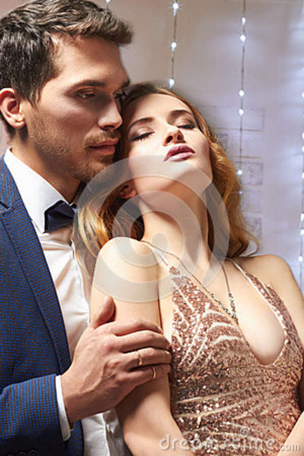 f3bf44afc8767 Young couple in love.Cheerful young couple in elegant evening dresses.  Fashion, glamour.hugging in christmas decorated interior