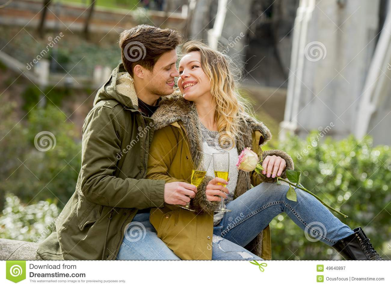 Young couple in love kissing tenderly on street celebrating Valentines day or anniversary cheering in Champagne