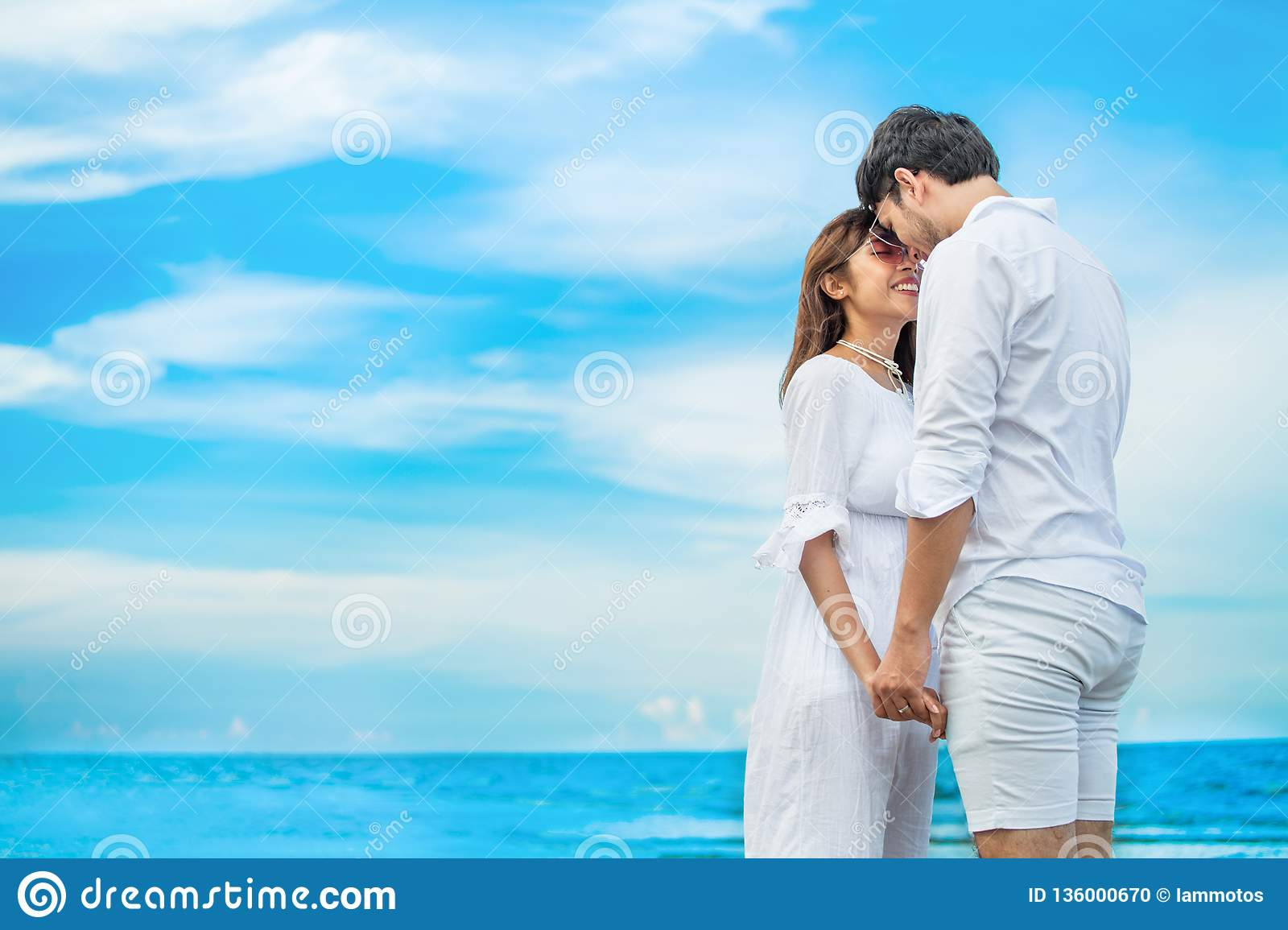 Young couple in love looking to each other and holding hand together at sea beach on blue sky .happy smiling young wedding with