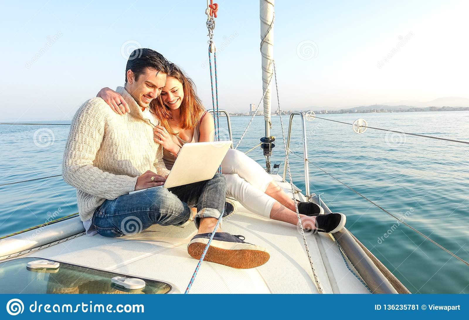 Young couple in love on sail boat having fun remote working at laptop- Happy luxury lifestyle on yacht sailboat