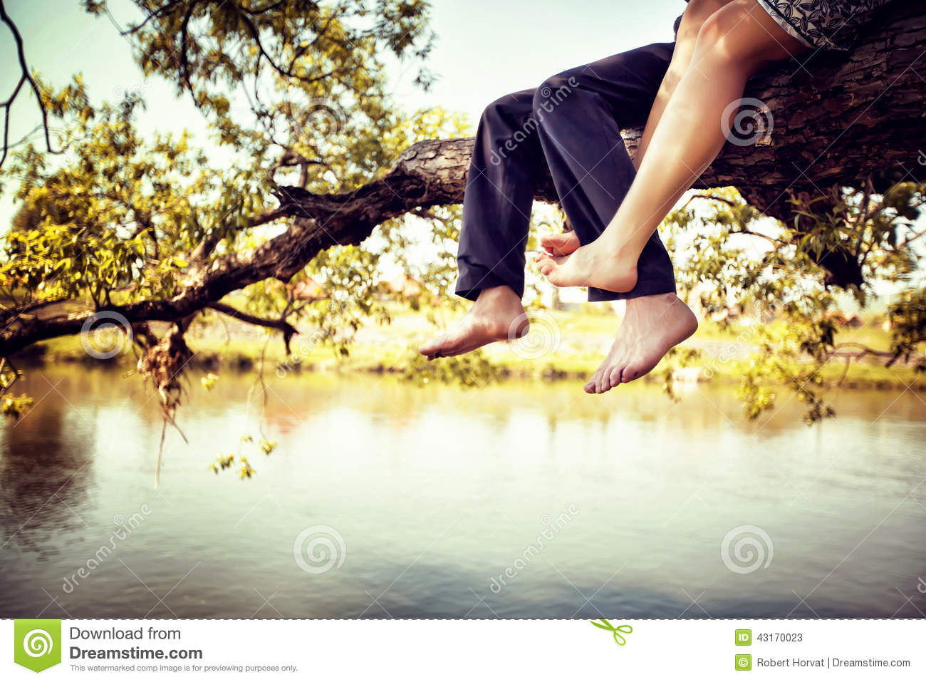 Young couple in love sitting cross-legged on a tree branch above the river in nice sunny day. Photo is colorized in warm tints