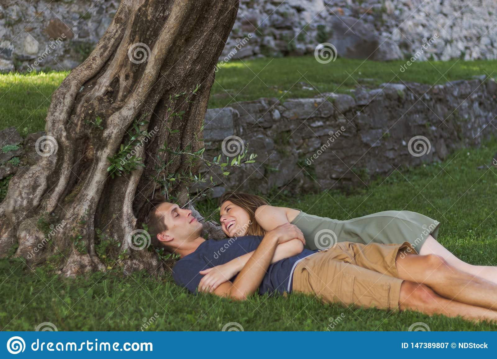 Young Couple in Love sitting under a tree in a castle
