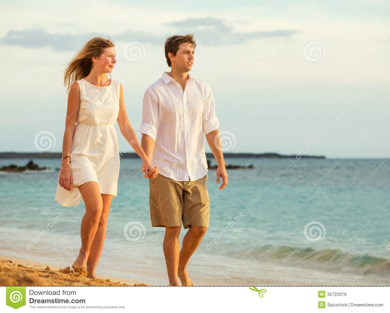 Young Couple In Love Walking On The Beach At Sunset Stock Photo