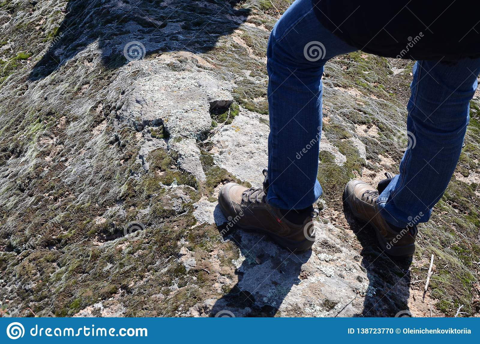 Male feet in boots.Climber on the top of rock.Relaxation after long walk