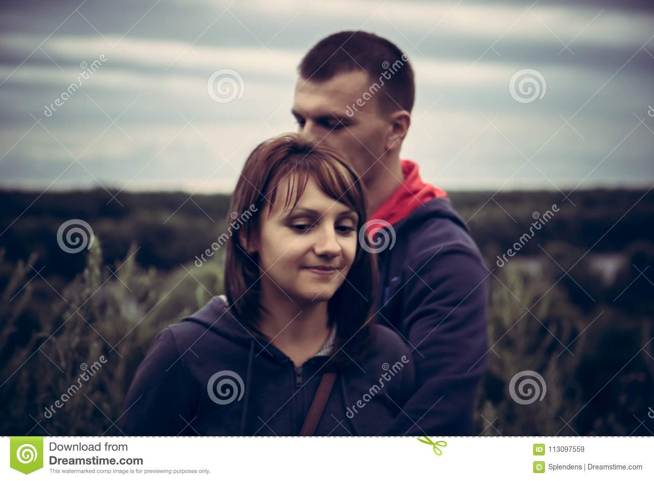 Young couple man woman together opposite dramatic sky concept love togetherness forgiveness