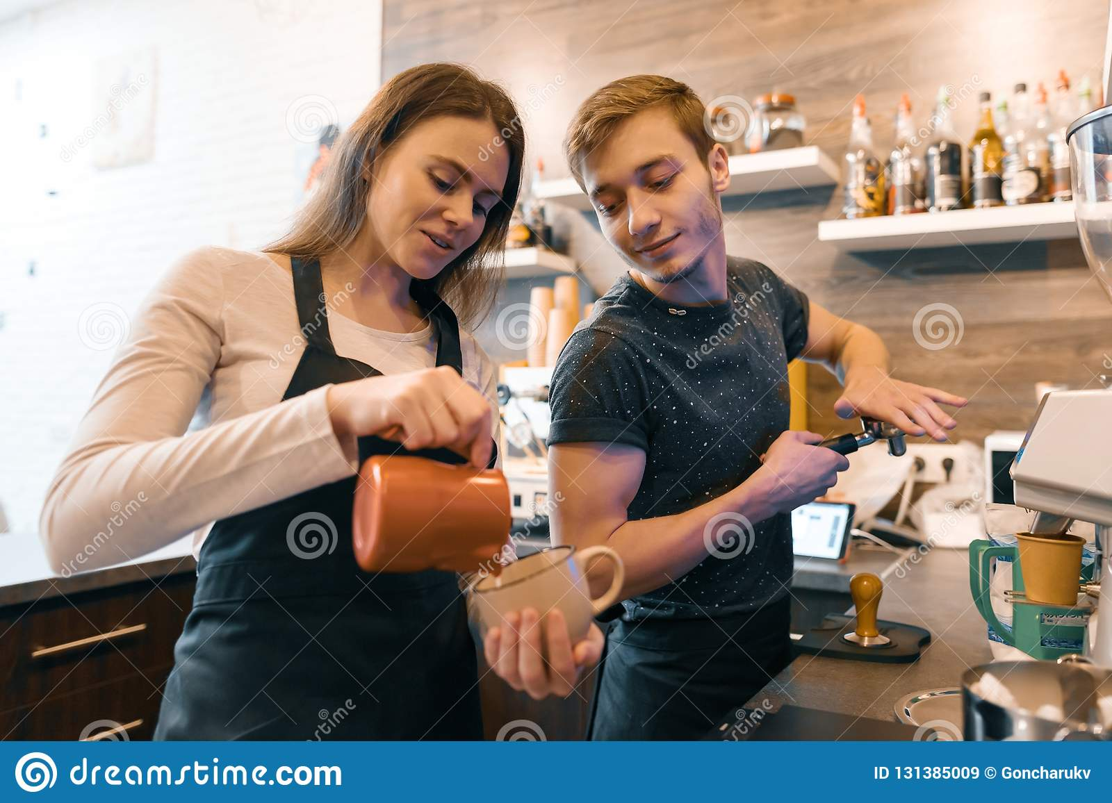 Young couple man and woman owners small business coffee shop, working near coffee machines, making drinks