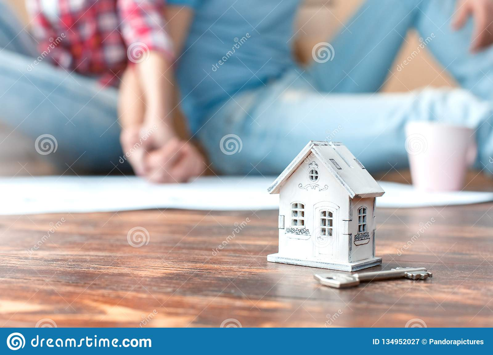 Young couple moving to new place sitting holding hands blurred house model close-up