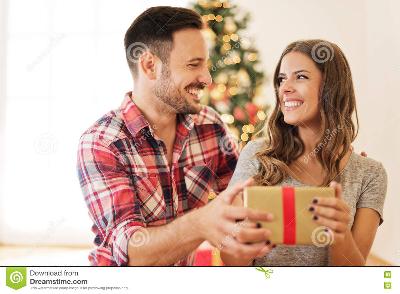young couple opening a christmas present on a christmas morning