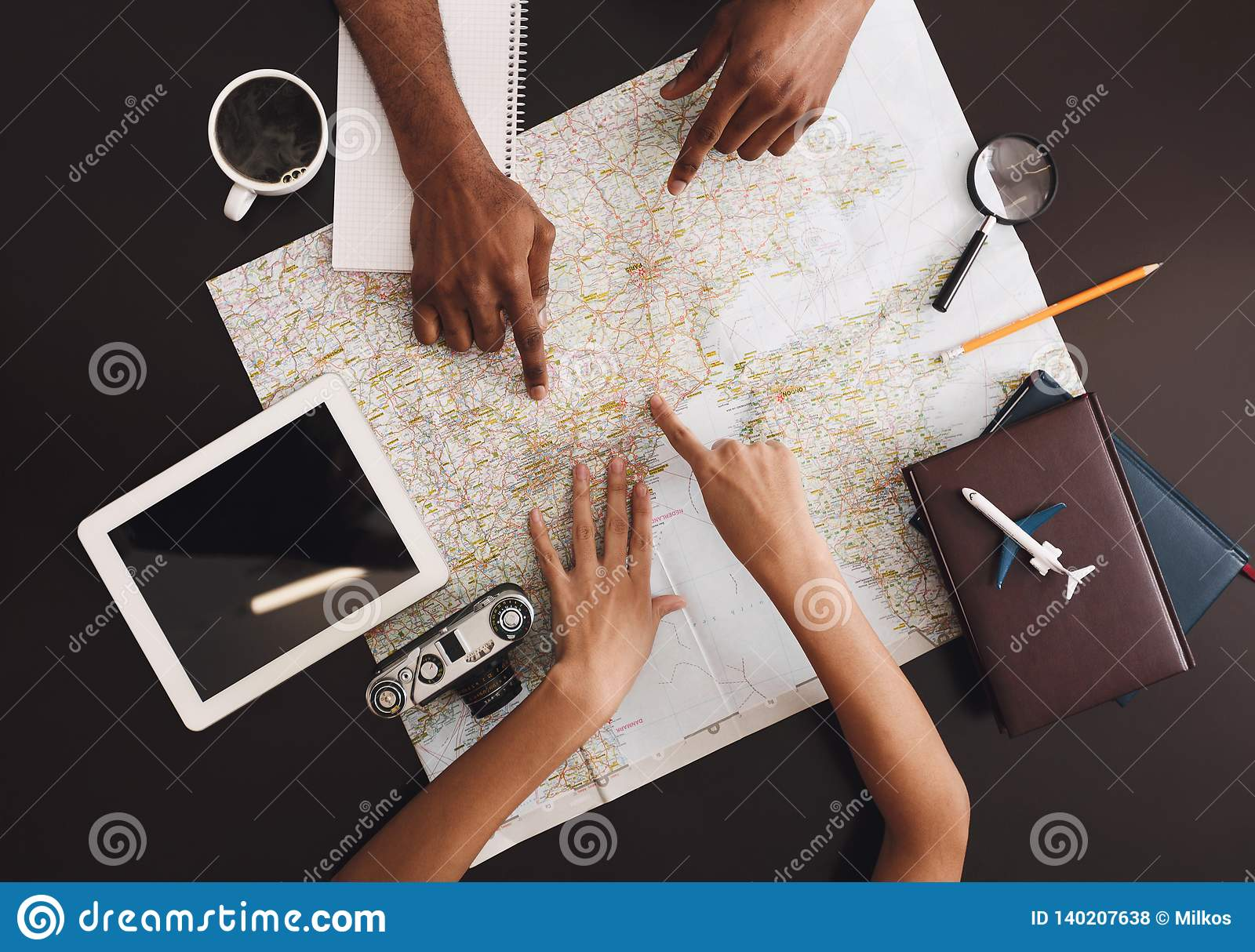 Young couple planning honeymoon vacation trip with map