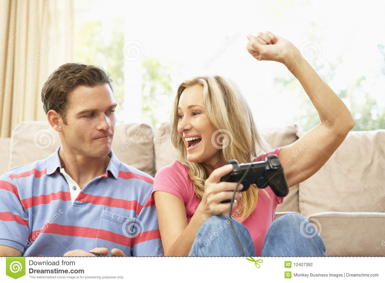 Stock photography young couple playing computer game on sofa at home