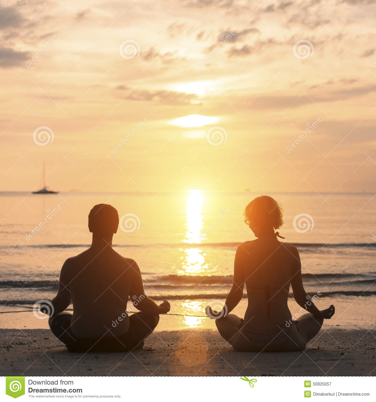 Young Couple Practicing Yoga On Sea Beach During Sunset