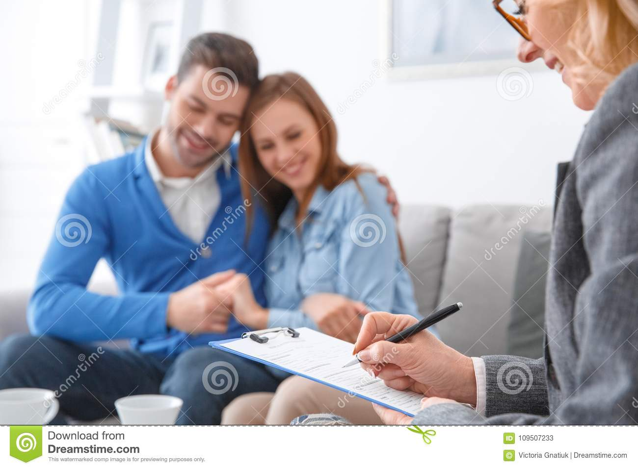 Young Couple With Psychologist Family Therapy Therapist Writing