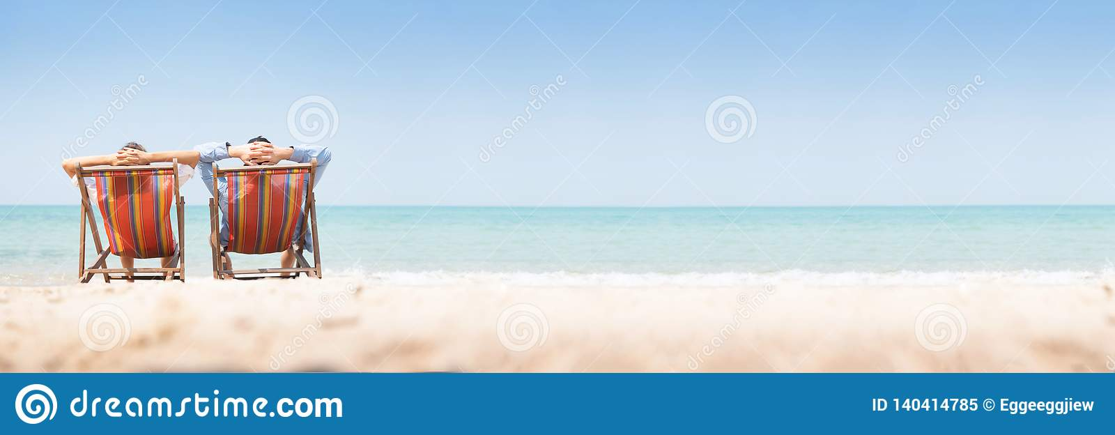Young couple relaxing on chair beach