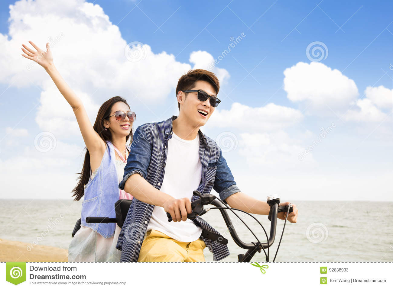 Young couple riding bicycle on the beach