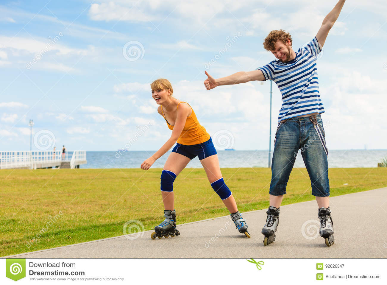 Young fit couple on roller skates riding outdoors on sea coast, women and  men rollerblading enjoying time together